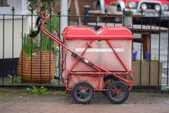 Chariot royal rouge à courrier enchaîné à la porte avec le jardin de bar à l'arrière-plan Photo stock