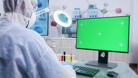 Chariot tiré du scientifique dans la combinaison blanche dactylographiant sur l'ordinateur vert d'écran banque de vidéos