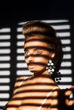 Charisma. Charming Woman's Face in Shadow of Roller Blind Royalty Free Stock Image