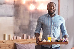 Charismatic African American man holding breakfast tray in the bedroom. Enjoying care about my love. Handsome positive inspired African American man standing in Royalty Free Stock Images