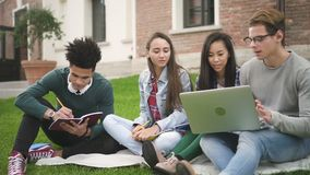 Charismatic american four person talking, sitting along college campus. Multiracial 20s friends in smiling discussion, writing, looking in computer. Friendly stock video footage