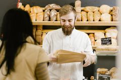 Charismatic baker with a beard and mustache gives a paper bag of bread to the customer in the bakery stock photography