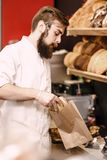 Charismatic baker with a beard and mustache puts fresh bread in a paper bag in the bakery royalty free stock image