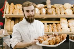 Charismatic baker with a beard and mustache stands with a tray with fresh pastries on the background of shelves with royalty free stock image