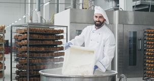 Charismatic baker chef unloaded the flour in a container in a big bakery industry he is smiling and have a great mood. Preparing the dough stock footage