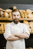 Charismatic baker stands on the background of shelves with fresh bread in the bakery royalty free stock photo