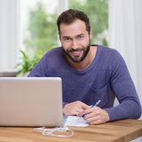 Charismatic bearded man working at a desk. In front of a woman looking at the camera with a warm friendly smile Royalty Free Stock Image