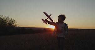 Charismatic boy playing with a red airplane at sunset , perfect view. Charismatic boy playing with a red airplane at sunset , perfect view stock footage