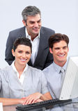 Charismatic business team working at a computer Royalty Free Stock Photos