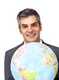 Charismatic businessman holding a terrestrial glob Royalty Free Stock Images