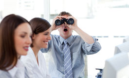 Charismatic businessman looking through binoculars Stock Images