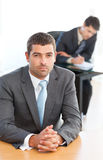 Charismatic businessman sitting in the foreground Royalty Free Stock Images