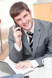 Charismatic businessman using laptop while phoning Stock Image