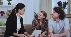 Charismatic couple have a discussion with a real estate agent representing the house plan at the end she make a great. Deal with her client shaking hands very stock video