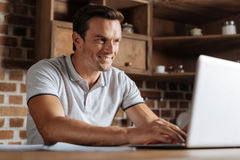 Charismatic devoted guy comfortably working from home Royalty Free Stock Photography
