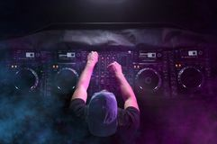 Charismatic disc jockey at the turntable. DJ plays on the best, famous CD players at nightclub during party. EDM, party concept. royalty free stock images