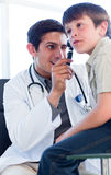 Charismatic doctor examining little boy's ears Royalty Free Stock Image