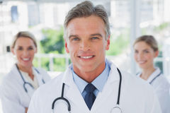 Charismatic doctor standing with colleagues Stock Photography