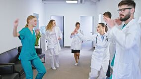Charismatic doctors and nurses dancing excited in the hospital corridor they enjoying the time at work