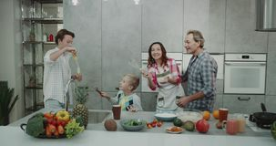 Charismatic family mature parents and two kids have a family time together playing in the kitchen with bubbles while stock footage