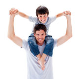 Charismatic father giving his son piggyback ride Royalty Free Stock Images