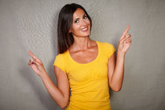 Charismatic female crossing fingers while wishing. Charismatic female in yellow blouse crossing fingers while wishing Stock Images