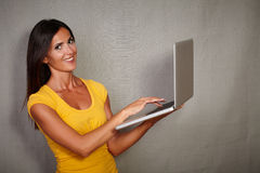 Charismatic female holding laptop while smiling Royalty Free Stock Images