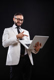 Charismatic guy in a suit with ntebook Stock Photography
