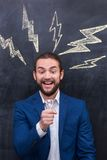 Charismatic handsome catch a bright idea. Excitement man with beard standing on theƒ blackboard background Stock Photo