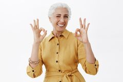 Charismatic, happy and energized cute elderly mother with gray hair in yellow trendy trench coat showing okay gestures stock image