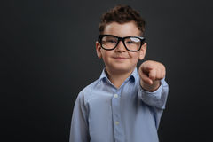 Charismatic inspiring kid pointing at you. You can do it. Sweet confident nice boy encouraging you doing something while wearing glasses and standing isolated on royalty free stock image