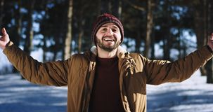 Charismatic with a large smile man enjoying the time in the forest on the winter time he take some fresh air and feeling. Good in front of the camera. 4k stock video footage
