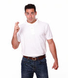 Charismatic latin male crossing his fingers Stock Images