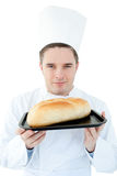 Charismatic male cook showing bread to the camera Royalty Free Stock Photo