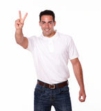 Charismatic male smiling with victory sign Stock Image