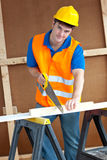 Charismatic male worker with hardhat sawing wood. Charismatic male worker wearing a yellow hardhat sawing a wooden board at work Royalty Free Stock Photos