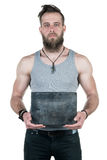 A charismatic man with a beard holds an empty gray plate for a copy space on a white isolated background. Vertical frame Royalty Free Stock Image
