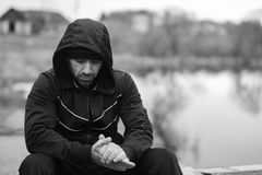 Charismatic man during a break by the lake. After hard running workout Stock Photography