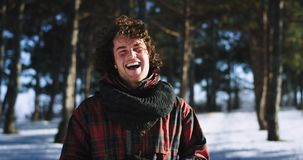 Charismatic man with curly hair smiling large and enjoying the moment while traveling alone in a the winter time. Portrait in front of the camera. slow motions stock video