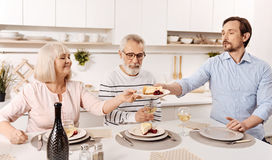 Charismatic man enjoying family dinner with parents at home Stock Images
