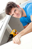 Charismatic man repairing his sink Royalty Free Stock Photo