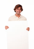 Charismatic man standing holding a blank placard. Royalty Free Stock Images