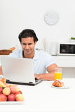 Charismatic man working on his laptop in kitchen. During breakfast Royalty Free Stock Photo