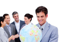 Charismatic manager and his team holding a globe Stock Photo
