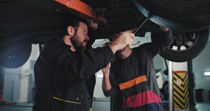 Charismatic mature man mechanic and his assistance in a modern auto service under the damaged car using a flashlight
