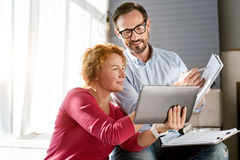 Charismatic middle aged couple sharing ideas at home Stock Photos