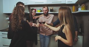Charismatic multi ethnic group of young people have a party time they chatting with each other and lift the glasses up. And cheers all together stock video footage