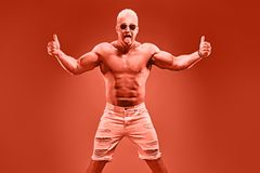 Charismatic Muscular athletic man jump naked torso. Charismatic Muscular man with naked torso jump showing tongue thumb up in fashion neon coral light. Sexy royalty free stock photography