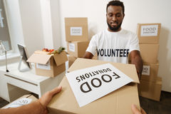 Charismatic optimistic man receiving another contribution. Benevolent endowment. Incredible attentive young gentleman working for welfare organization and Royalty Free Stock Photography
