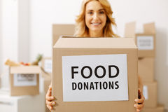 Charismatic pretty lady happy working for community. Noble intentions. Altruistic active cute woman holding a box full of food she wanting sending to those in Stock Image